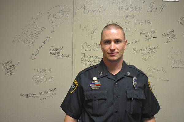 School Resource Officer Aaron Leisinger in Officer Hansels office in front of a board full of messages left by students for Hansel.