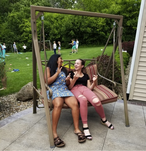 Socialize.+Friends+Venna+Venkatesh+and+Shelby+Cook+sit+on+the+porch+swing%2C+enjoying+conversation+and+the+great+weather.++