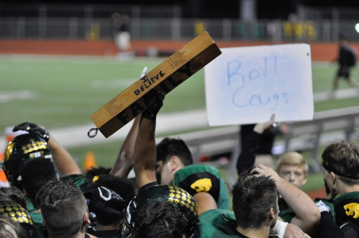 The Family stick raised above the huddle after the Kennedy Cougars defeated the Linn Mar Lions.