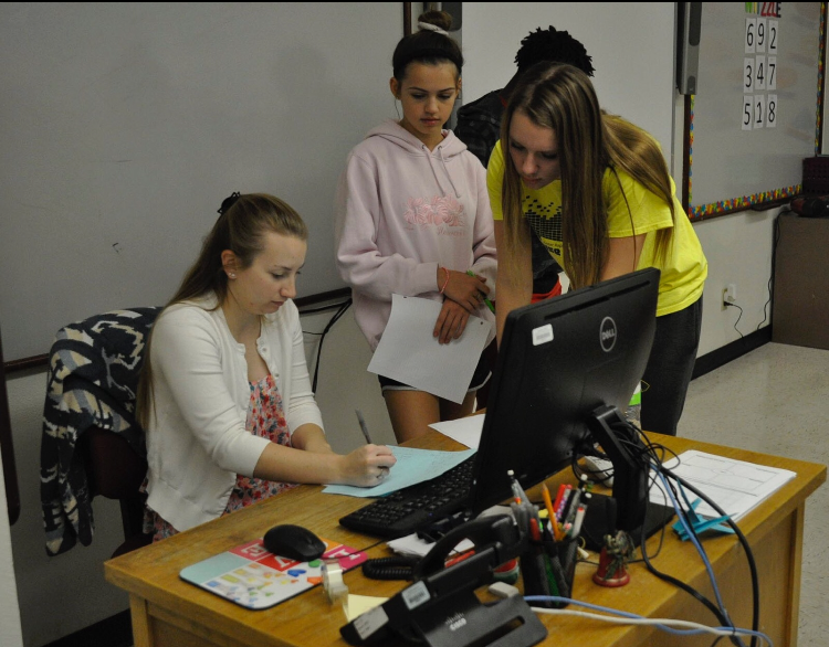 Math teacher Emily Reminiskey helps her students Grace Hanrahan, fr., and Bella Deleon, fr., with algebra classwork.