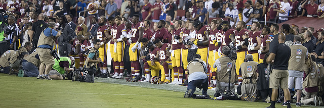 Washington Redskins teammates during the national anthem before a game against the Oakland Raiders at FedExField on September 24, 2017 in Landover, Maryland.