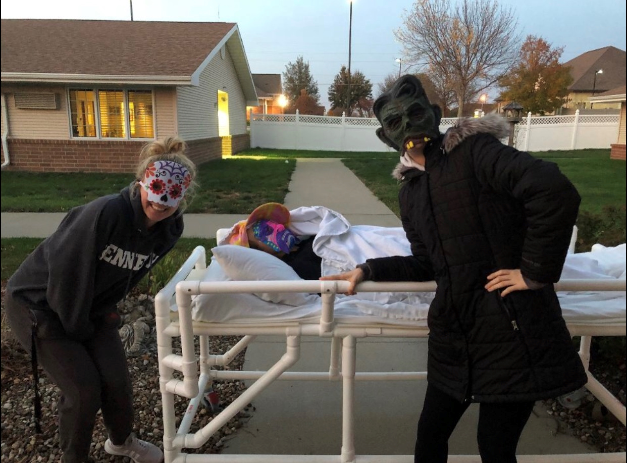 Hailey Dolphin, sr., and Olivia Haefner, jr., pose next to Gwyn Smith, jr., as she waits to put on a scare.