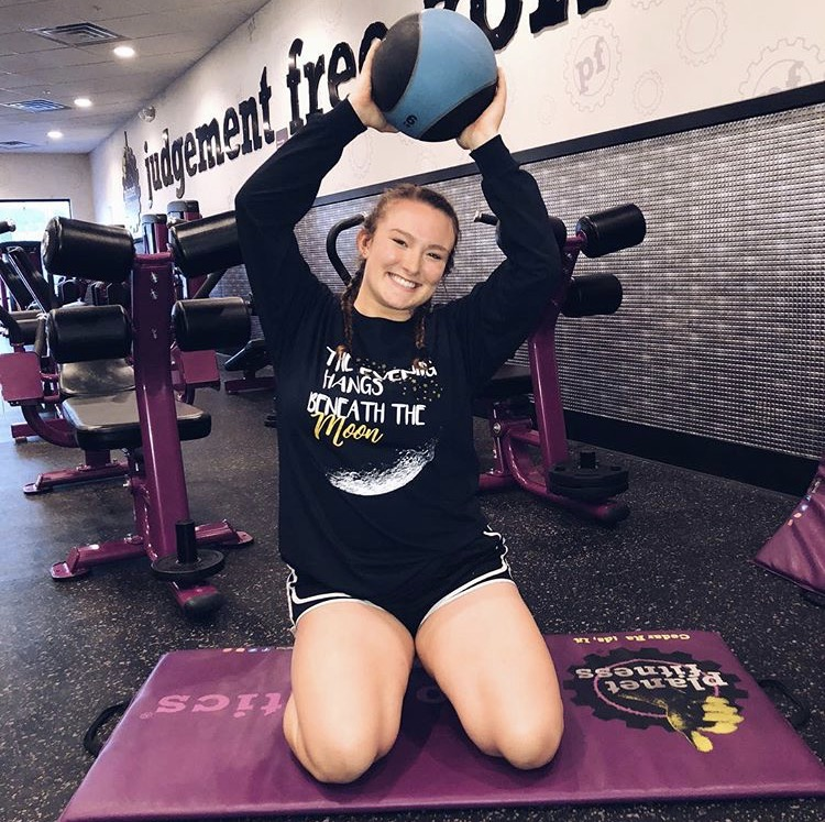 Senior Taylor Mather posing with a medicine ball at Planet Fitness in Cedar Rapids.