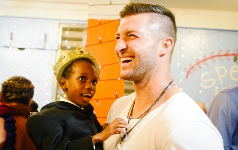 Tim Tebow with a child from Night to Shine event.
