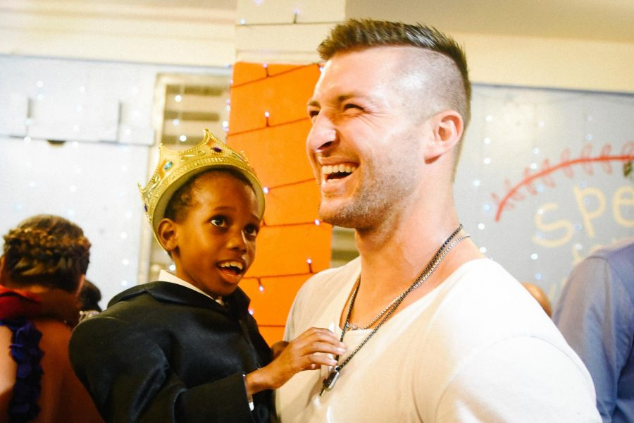 Tim+Tebow+with+a+child+from+Night+to+Shine+event.+