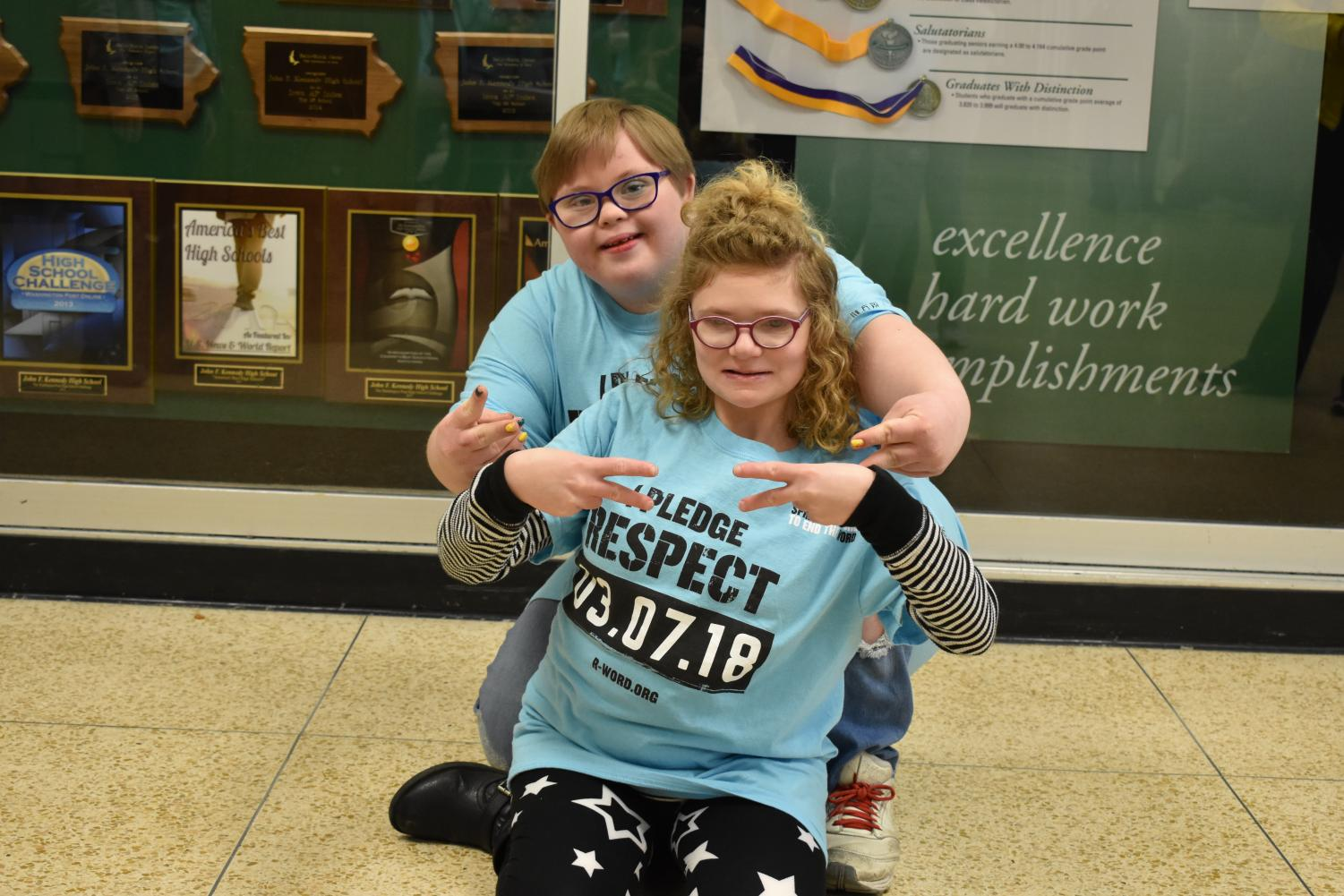 Destiny Dostal, so., and Ellie Grovert, sr., throw up some peace signs.