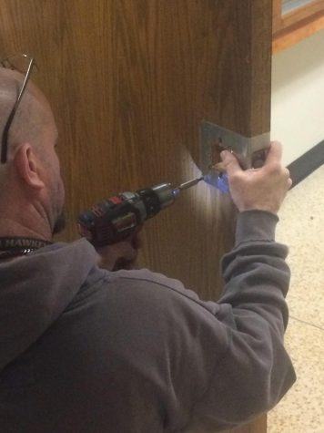 District facility technician changing the door knobs.