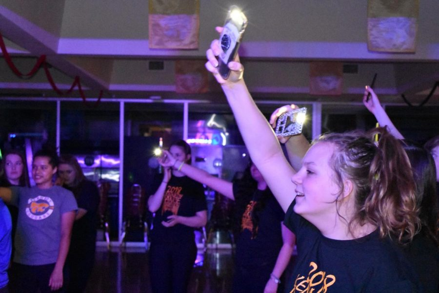 Laura Shook, jr., waving her phone with the flashlight on for the karaoke singing.
