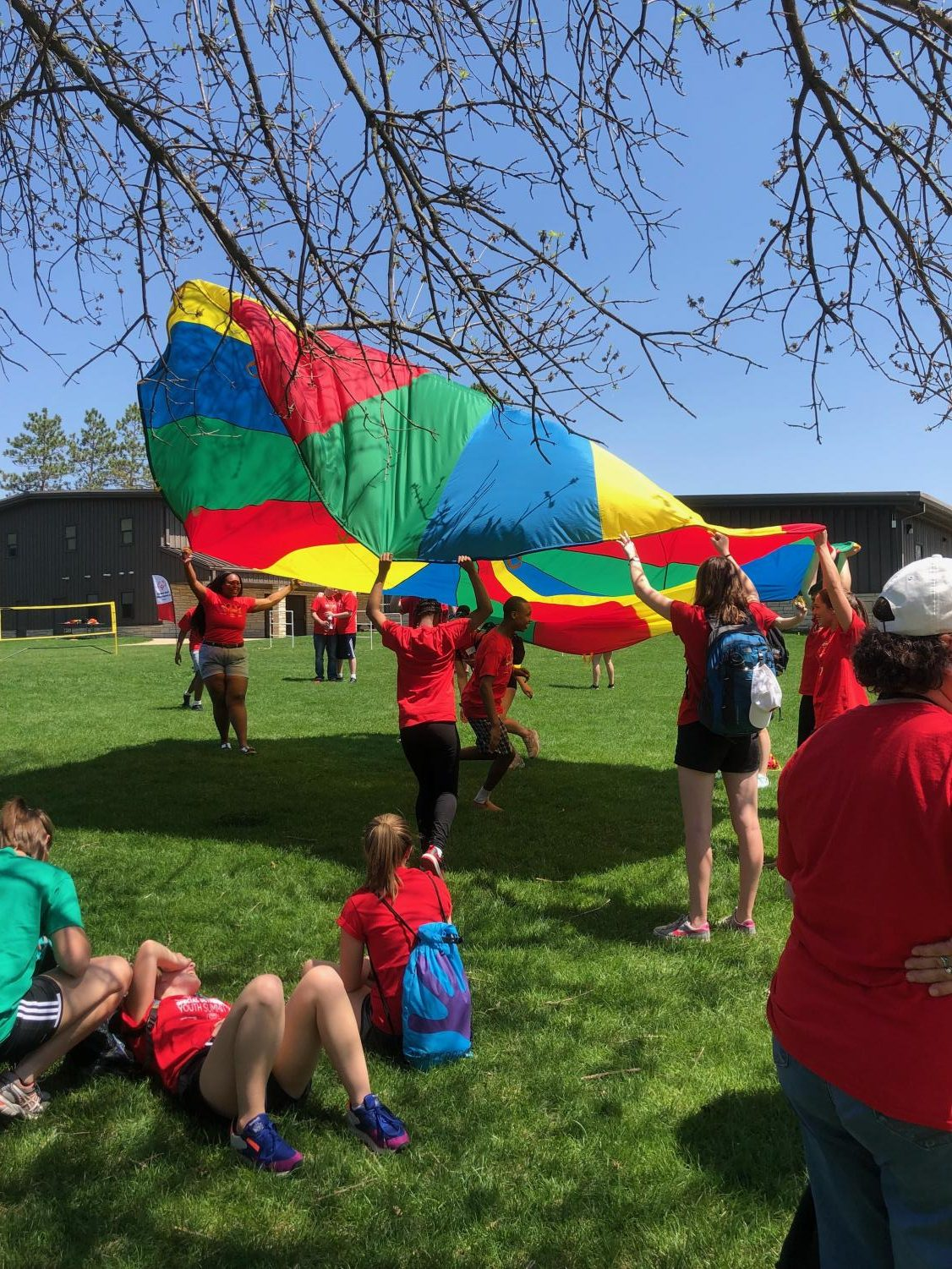 Students with and without IDD playing with a parachute at Camp Courageous