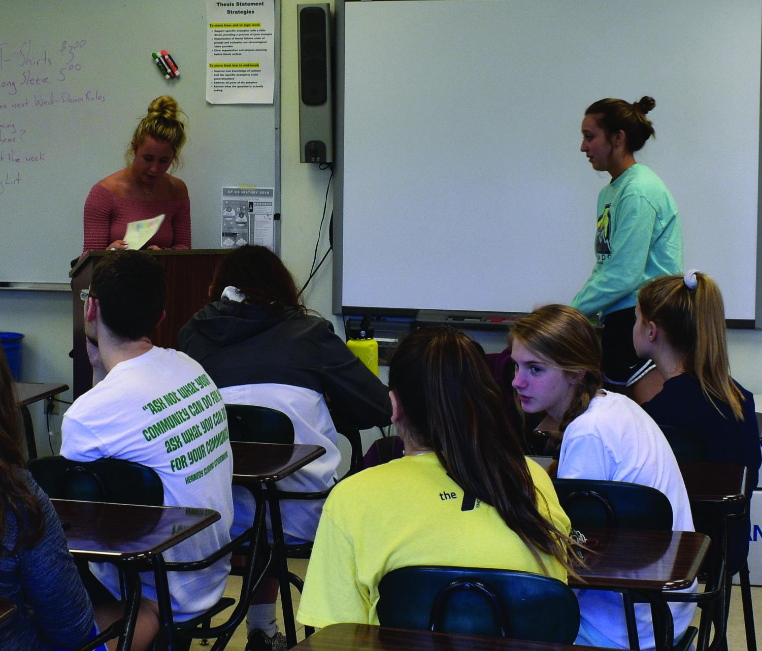 Seniors Hailey Dolphin and Evyn DeWitte take attendance at the start of class and give announcements.