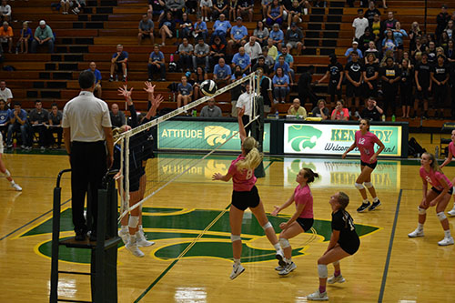 Jenna Anderson, sr., hitting the ball over the net.