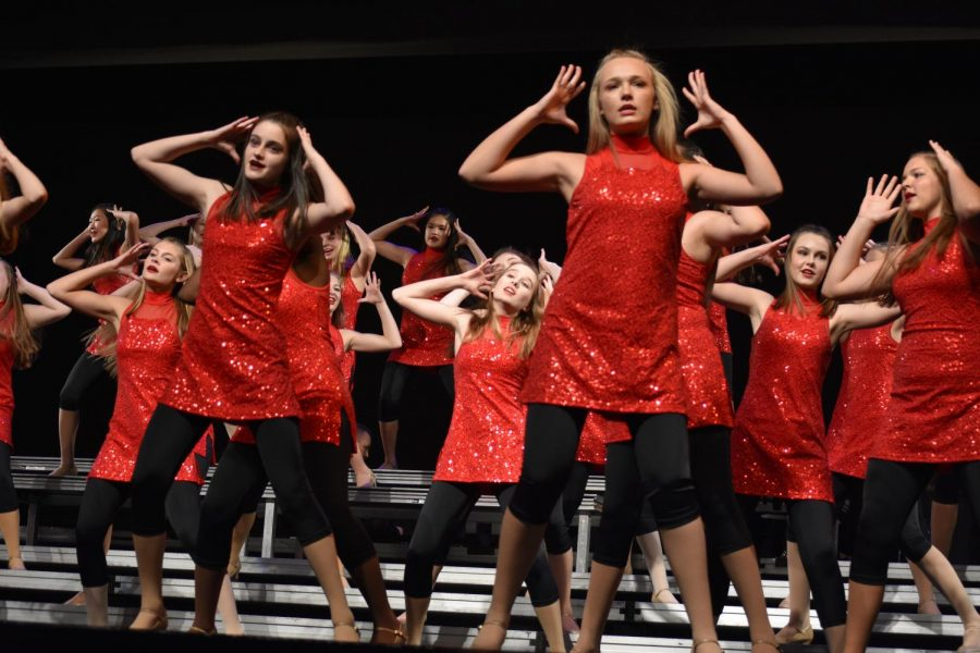 Chanteurs singing and dancing in their red outfits.