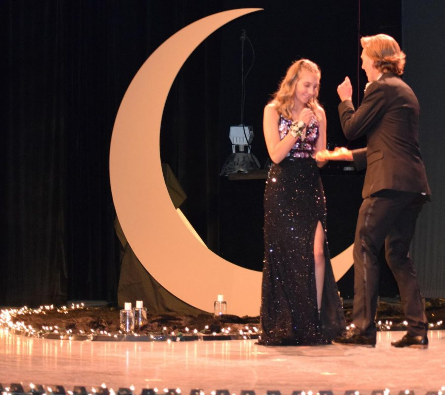 Senior Anna Reinhart and senior Ryan Huber doing a handshake during grand march.