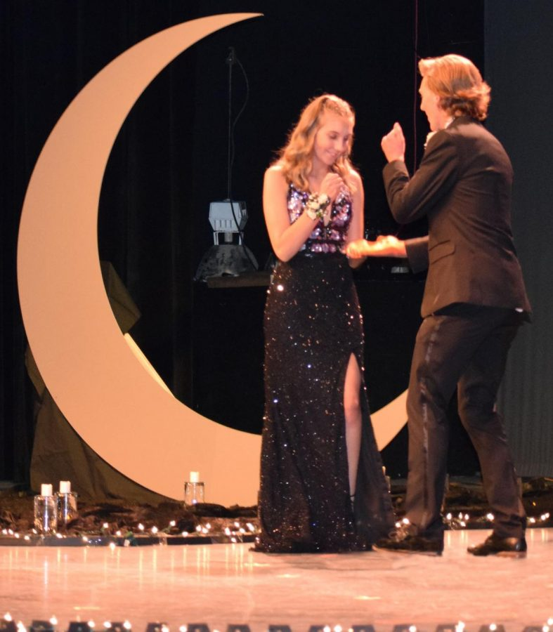 Senior+Anna+Reinhart+and+senior+Ryan+Huber+on+stage+at+Grand+March+doing+a+handshake.