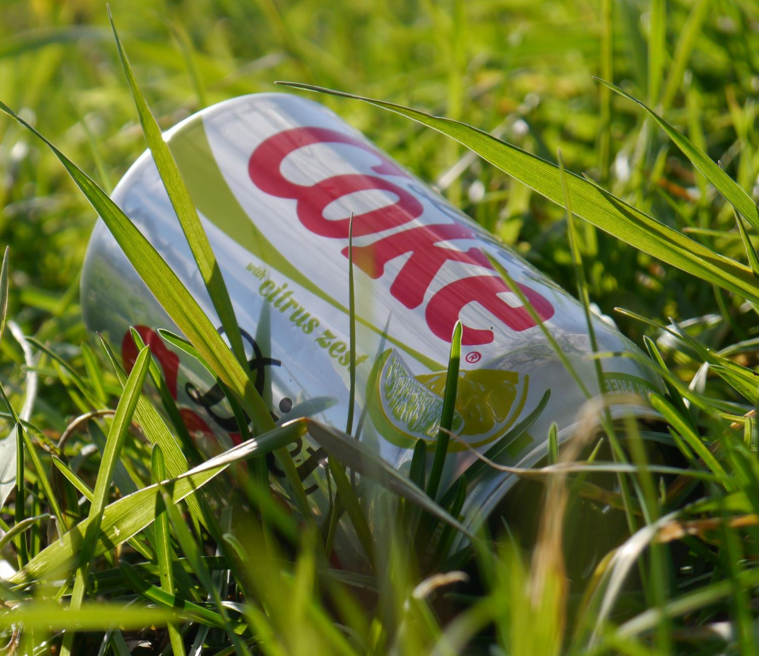 A Coca-Cola can found outside in the grass from littering.