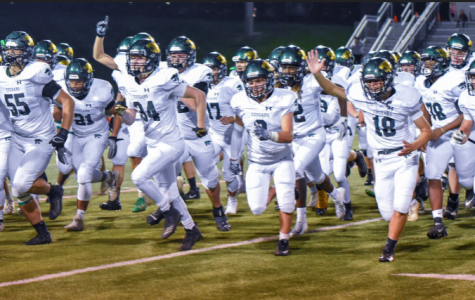 The Kennedy Varsity Football team running towards the student section after winning their latest game against the Linn Mar Lions.