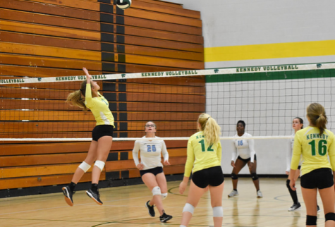 The Kennedy volleyball team spiking the ball at their game.