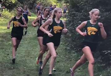 The Kennedy Girl's Cross Country team racing down the winding path at their meet.