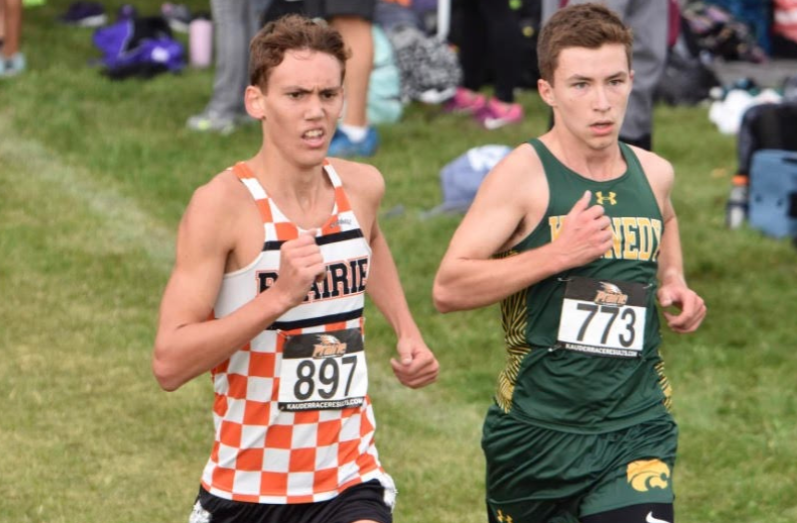 Jacob Green, sr., running in his green and gold uniform at a cross country meet along side a Prairie runner.