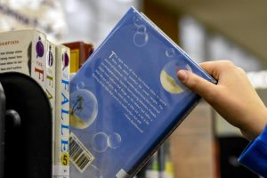 A student at Kennedy High School pulling a book off of the shelf.