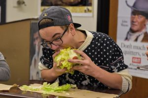 A Lettuce Club participant takes a big bite of lettuce.
