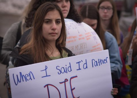 "Mawadda Tawil, jr. holds up a sign that reads ""When I said Id rather die than go to math class, I was joking."""