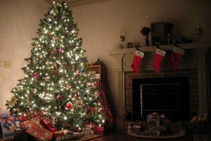 Christmas stockings and presents surround a lit up Christmas tree.