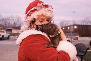 Some students brought pets with them to the drive-thru. Mrs. Claus holds a student's puppy, named Kinnick.