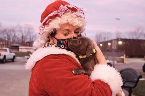 Some students brought pets with them to the drive-thru. Mrs. Claus holds a student