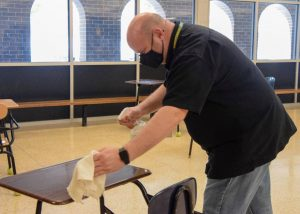 Shawn Thomsen, facilitator at Kennedy High School, disinfecting a desk to help protect students and staff from the ongoing threat of illness.
