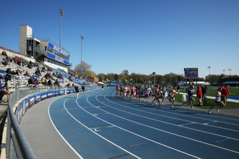Competitors in the boys' 3200 meter race run past partially-empty stands at Drake Stadium in Des Moines.