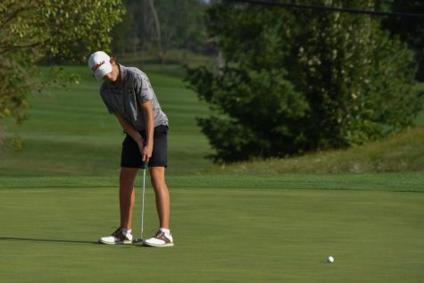Sophomore Reid Hall putts while on a Ellis Golf Course green.