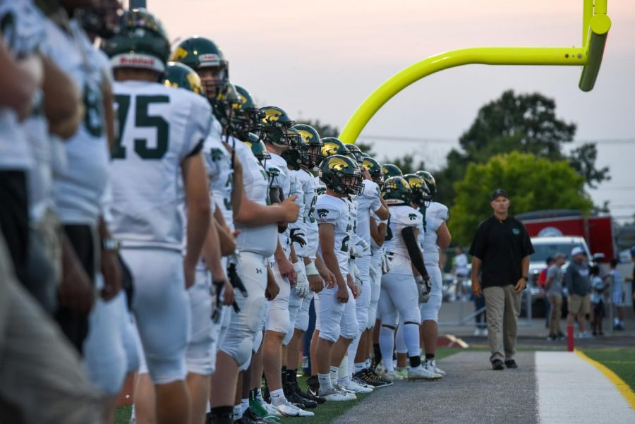 The Kennedy Football team lines up along the edge of the field before warmups.