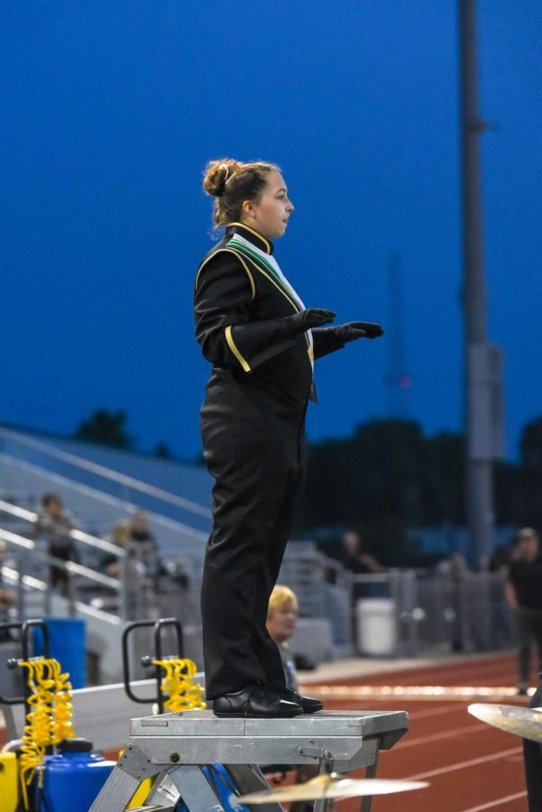 Junior Gwen Canney conducts the marching band.