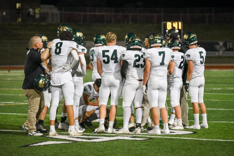 The Kennedy football team huddles on the field during a timeout.